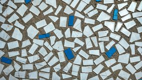 Old tiles in concrete, mosaic, broken ceramics in the building. Background of a house in the city. Old tiles in concrete, mosaic, broken ceramics in building Royalty Free Stock Photos