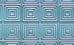Old tiles on the wall with a unique square pattern. Old tiles on the wall with a unique square pattern, turquoise color Stock Image