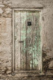 Old timber door in the scuffed wall Royalty Free Stock Images