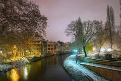 Old timber-framing houses in Petite France quarter, Strasbourg. Snow-covered roofs and refctions in the river water. Night scene. Christmas time Stock Images