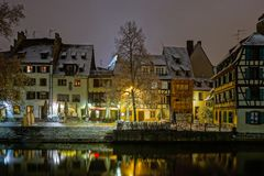 Old timber-framing houses in Petite France quarter, Strasbourg. Snow-covered roofs and refctions in the river water. Night scene. Christmas time Stock Photos