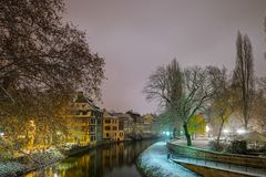 Old timber-framing houses in Petite France quarter, Strasbourg. Snow-covered roofs and refctions in the river water. Night scene. Christmas time Stock Image