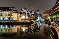 Old timber-framing houses in Petite France quarter, Strasbourg. Snow-covered roofs and refctions in the river water. Night scene. Christmas time Stock Photo