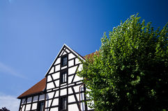 Old timber house. Old architecture of Poland, timber wall of a house with a green tree and clear blue sky Stock Photos