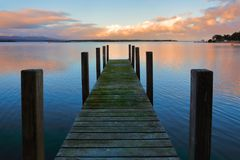 Mossy jetty at sunset. Old timber jetty with green mossy planks in the sunset Stock Images