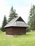 Old timbered village house in open-air museum. Old wooden village house with shingles roof with pine trees behind in open-air museum Liptov Village Museum Stock Image