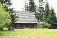 Old timbered village house in open-air museum. Old wooden village house with shingles roof with pine trees behind in open-air museum Liptov Village Museum Royalty Free Stock Images