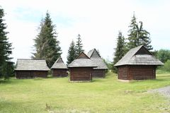 Old timbered village houses in open-air museum. Old wooden village houses with shingles roofs among pine trees in open-air museum Liptov Village Museum Pribylina Royalty Free Stock Image