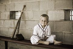 Old Time Baseball. Adorable preschooler dressed in a vintage baseball uniform in a dugout. Desaturated color to give the image a vintage feel royalty free stock photos