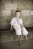 Old Time Baseball. Adorable preschooler dressed in a vintage baseball uniform in a dugout. Desaturated color to give the image a vintage feel stock photo