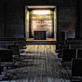 That Old Time. Interior of old church with wooden pews, wooden floor and alter with cross above, very rustic and simplistic Stock Photo