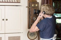 Old Time Landline. A woman in period dress talking on an old-fashioned antique wall phone royalty free stock photo