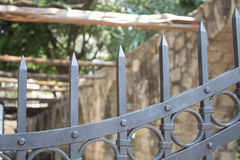 Old Time Security. An iron gate guards the courtyard of Mission Valero The Alamo. Rustic architecture fades into the background Royalty Free Stock Photo