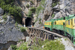 Old-time green and yellow train going into a tunnel. An old-fashioned train going up a mountain crosses a trestle bridge and approaches a tunnel in Alaska Stock Photo