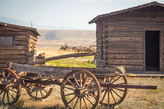 Old Time Vintage Antique Wood Wagon and Log Cabins. Abstract of Vintage Antique Wood Wagon and Old Time Log Cabins royalty free stock photography