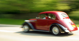Old-timer on the way. Red old-timer in speed Stock Photography