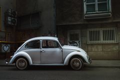 White Volkswagen Beetle parked in the middle of the city royalty free stock photography