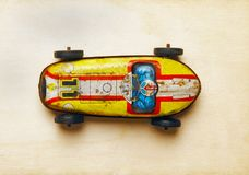Old tin car. Old tin toy  car on a wood background shot from above Royalty Free Stock Image