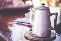 Old tin tea or coffee pot on wooden table Stock Photo