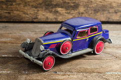 Old tin toy on old wood background. Stock Photos
