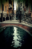 Old tiny bridge in venice, italy. Dark water Royalty Free Stock Images