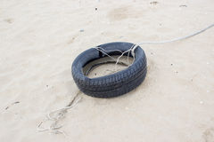 Old tire buried in beach Royalty Free Stock Photos