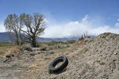 Old tire by dirt pile. An old abandoned tire by a pile of dirt near Bishop California with trees and mountains in the background royalty free stock images