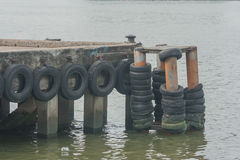Old tire on harbor in river. Stock Photography