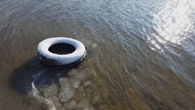 Old tire under snow in river sand in winter time. stock video footage