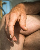Old Tired hands across legs. Hands belongs to a long time craftman Royalty Free Stock Image