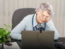 Old tired teacher is waiting online lesson Royalty Free Stock Photo