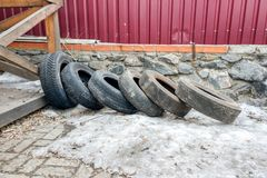 Old tires lie on the snow next to a stone fence and a wooden arbor. Old dirty tires lie on the snow next to a stone fence and a wooden arbor royalty free stock photography