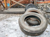 Old tires lie on the snow next to a stone fence and a wooden arbor. Old dirty tires lie on the snow next to a stone fence and a wooden arbor stock photography