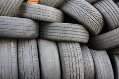 Old tires. Pile of old tires with red bricks in the background Royalty Free Stock Photo