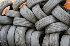 Old tires. Pile of old tires with red bricks in the background Stock Photography