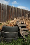Old tires & wood pallet & fence. Old tires and an old wooden pallet are covered with dead branches and sit in iceplant by a fence. Junky yard Royalty Free Stock Photos