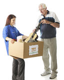 From the Old to the Young. A young teen holding a large box with a holiday Toy Donations sign as an elderly men is donating a toy guitar.  Focus on girl,  On a Stock Photos