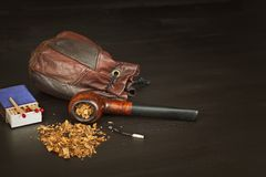 Old tobacco pipe and spilled tobacco, used on a black wooden background. Shabby old tobacco pipe. Stock Images