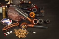 Old tobacco pipe and spilled tobacco, used on a black wooden background. Shabby old tobacco pipe. Stock Image