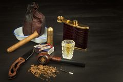 Old tobacco pipe and spilled tobacco, used on a black wooden background. Shabby old tobacco pipe. Stock Photo