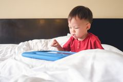 Old toddler boy child sitting in bed watching a video from tablet pc. Cute little Asian 2-3 years old toddler boy child sitting in bed watching a video from stock image