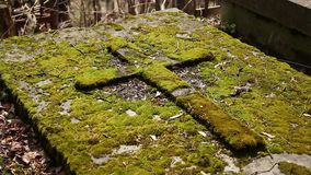 Old tomb with cross covered green moss