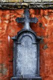 Old gravestone with cross in front of crumbling facade stock image