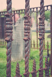 Old Tombstone Behid Rusty Fence Royalty Free Stock Photography