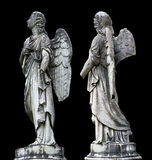 Old tombstone sculptures of an angel with broken arm and wings isolated on black. Royalty Free Stock Photo