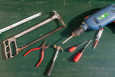 Old tools. On green wooden surface stock image