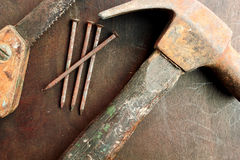 Old Tools. Old hammer nails and a small hand saw Royalty Free Stock Photo
