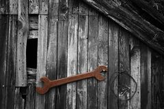Old Tools. Old rusty tool on a high-contrast BW cottage wall Royalty Free Stock Images