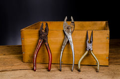 Old tools. Old carpenter tools on wooden background,rust pliers royalty free stock images