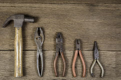 Old tools. Old carpenter tools on wooden background,rust pliers stock image
